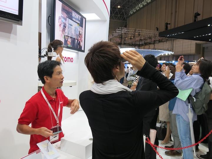 『インテリジェントグラス』で動画を見ている立澤氏。会場の天井あたりに大画面が見えています。